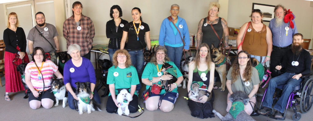 Sixteen people and almost as many dogs pose in two rows in a panaramic view of smiling convention-goers.