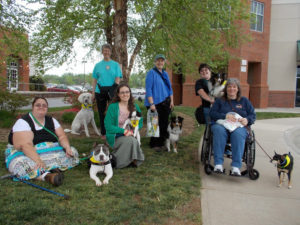 Six psychiatric service dog handlers smile brightly for the camera amid grass and trees, with red brick buildings in the background.