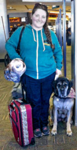 Kelsey and Kona stand with luggage at the airport, ready for equal ACAA access.