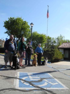 Four service dog teams smile amicably on a clear day.